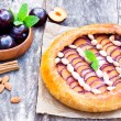 Homemade plum pie with almonds on the table — Stock Photo #72899287