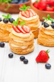 Homemade puff pastry stuffed with cream and berries on white tab — Stock Photo