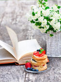 Puff pastry with berries old book and beautiful bouquet of white — Stock Photo