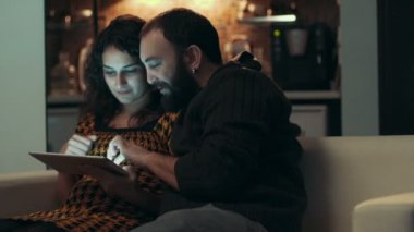 Couple using tablet on sofa at night in room — Stok video