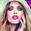 High fashion look.glamor closeup portrait of beautiful sexy stylish blond young woman model with bright makeup and pink lips with perfect clean skin in hat near summer flowers — Stock Photo #53967637