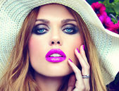High fashion look.glamor closeup portrait of beautiful sexy stylish blond young woman model with bright makeup and pink lips with perfect clean skin in hat near summer flowers — Foto de Stock