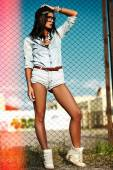 Portrait of sexy urban modern young stylish woman girl  model in casual jeans shorts  cloth outdoors in the street in black cap  behind blue sky — Stock Photo