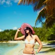 High fashion look.glamor sexy sunbathed model girl in white lingerie bikini in colorful sunhat behind blue beach ocean water near tropic palms — Stock Photo #61750451