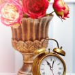 Classic clock  watch in bright colorful retro interior behind red flowers — Stock Photo #61750229