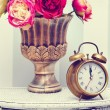 Classic clock watch in bright colorful retro interior behind red flowers — Stock Photo #61750231