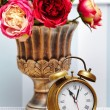 Classic clock  watch in bright colorful retro interior behind red flowers — Stock Photo #61750233