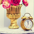 Classic clock  watch in bright colorful retro interior behind red flowers — Stock Photo #61750243