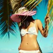 High fashion look.glamor sexy sunbathed model girl in white lingerie bikini in colorful sunhat behind blue beach ocean water near tropic palms — Stock Photo #61750407