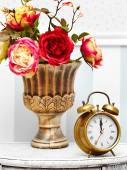 Classic clock  watch in bright colorful retro interior behind red flowers — Foto de Stock