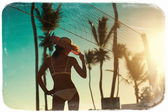 Photo in retro style  of sexy model girl in white bikini with volleyball net on beach and palms behind blue summer sky — Stock Photo