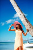 Hot beautiful woman in colorful sunhat and dress walking near beach ocean on hot summer day near palm — Stock Photo