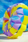 Bright colorful Rainbow Parachute on the beach behind blue ocean water — Stock Photo