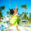 Happy urban modern young stylish woman girl model in bright modern cloth in green colorful skirt outdoors in the summer beach jumping behind blue sky — Stock Photo #62845121