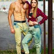 High fashion look.beautiful couple sexy stylish blond young woman model with bright makeup with perfect sunbathed skin and handsome muscled man in vogue style in jeans outdoors — Stock Photo #64671073