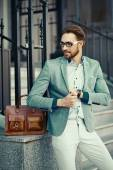High fashion look.Young stylish confident happy handsome businessman model  in suit cloth lifestyle in the street in sunglasses — Stock Photo