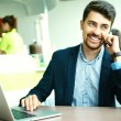 Young fashion smiling hipster man  in the city cafe during lunch time with notebook in suit speaking on phone — Stock Photo #78595540