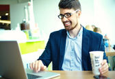 Young fashion smiling hipster man drinking  coffee in the city cafe during lunch time with notebook in suit — Stock Photo