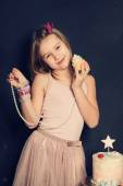 Young smiling girl with cupcake,  birthday card — Stock Photo