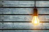 Light bulb lamp on wooden background with copy space — Stock Photo