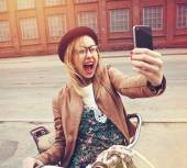City lifestyle stylish hipster girl with bike using a smartphone — Stock Photo
