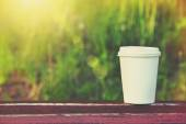 Paper cup of coffee on natural morning background — Stock Photo