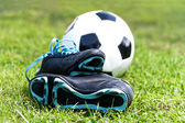 Soccer ball and shoes in grass — Stock Photo