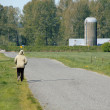 Single Woman on a Rural Road — Stock Photo #70535771