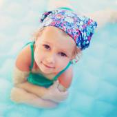Smiling little girl in the swimming pool at summer — Stock Photo