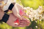 Hands of couple holding paper hearts — Stock Photo