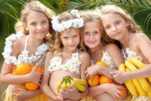 Portrait of four girls in a tropical style — Stock Photo