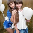 Portrait of a little girls in a field with white balloons — Stock Photo #55128977