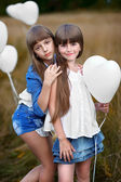 Portrait of a little girls in a field with white balloons — Stockfoto