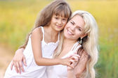 Young mother hugging her daughter in summer nature — Stock Photo