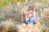 Portrait of a boy and girl on the field in summer — Stock Photo