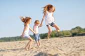 Three children playing on beach in summer — ストック写真