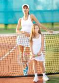 Portrait of mother and daughter on the tennis court — Fotografia Stock