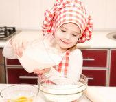 把面粉烘焙饼干的厨师帽带微笑的小女孩 — 图库照片