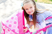 Cute smiling little girl playing with her toy carriage — Foto Stock