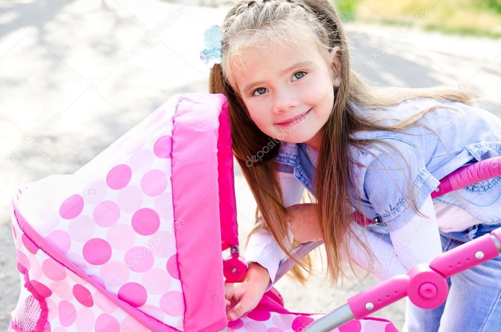 可爱微笑的小女孩玩她的玩具马车