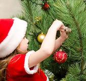 маленькая девочка в шляпе санта украшения рождественская елка — Стоковое фото
