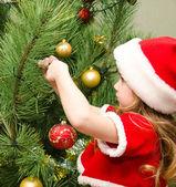 Malá holčička v santa hat zdobení vánočního stromku — Stock fotografie