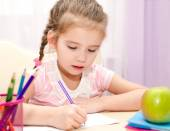 Cute little girl is writing at the desk — Stock Photo