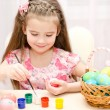 Cute little girl painting colorful easter eggs — Stock Photo #63879349