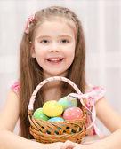 カラフルなイースターエッグの完全なバスケットとかわいい女の子 — ストック写真
