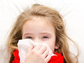 Little girl lying in the bed and blowing her nose — Stockfoto