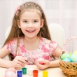 Smiling little girl painting colorful easter eggs — Stock Photo #66483907