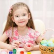Smiling little girl painting colorful easter eggs — Stock Photo #66483989