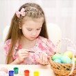 Smiling little girl painting colorful easter eggs — Stock Photo #66484411