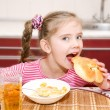 Cute smiling little girl having breakfast cereals with milk — Stock Photo #68552345